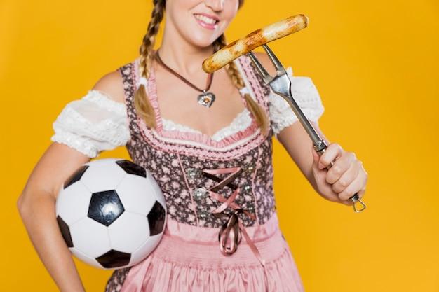 Giovane donna con salsiccia e palla