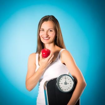Giovane donna con scala sotto il braccio e la mela