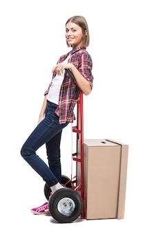Giovane donna con scatola di carta e un carrello a mano.