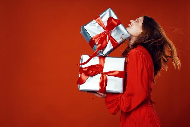 Giovane donna con scatole di regali nelle sue mani in bellissimi abiti, vendita di regali, buon natale e capodanno