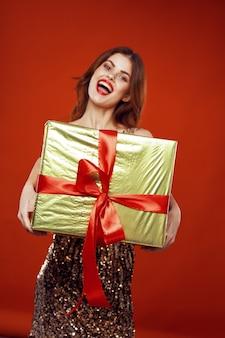 Giovane donna con scatole di regali nelle sue mani spazio su uno spazio colorato in abiti belli, vendita di regali, buon natale e capodanno