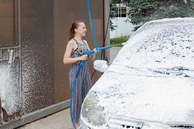 Giovane donna con secchio e straccio lavaggio auto