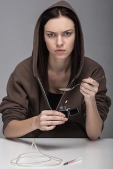 Giovane donna con siringa e droghe.