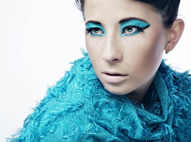 Giovane donna con sorprendente acconciatura in abito blu.