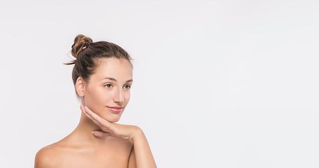Giovane donna con spalle nude su sfondo bianco