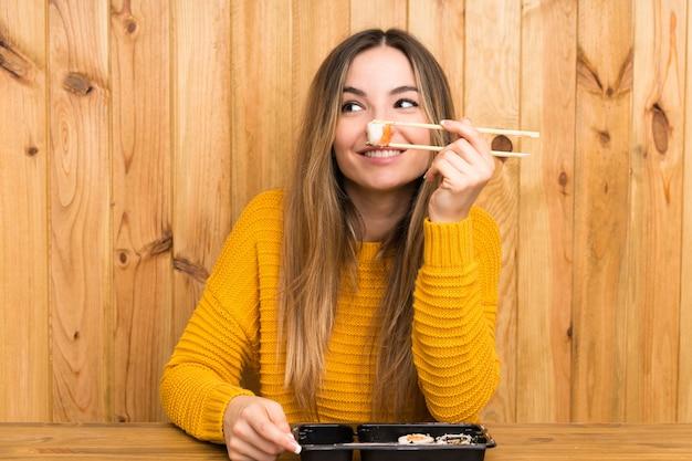 Giovane donna con sushi su legno