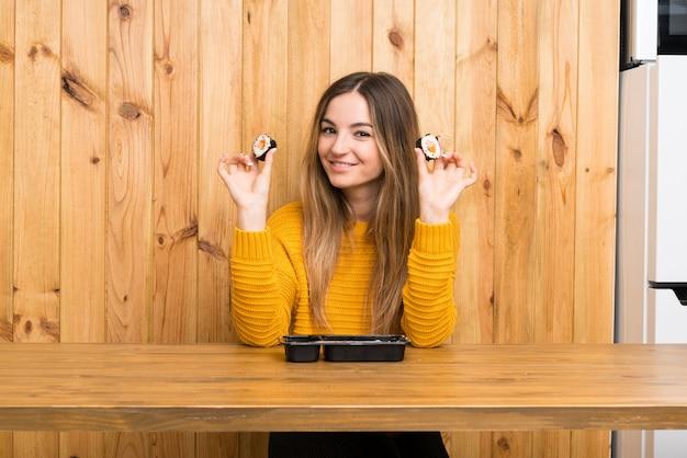 Giovane donna con sushi sulla parete di legno