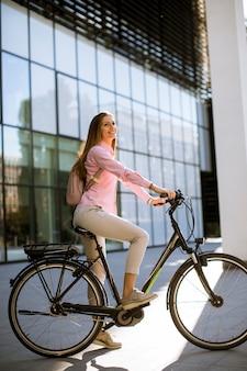 Giovane donna con tablet e e-bike all'aperto