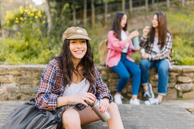 Giovane donna con thermos vicino agli amici
