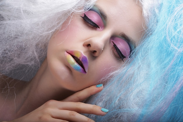 Giovane donna con trucco luminoso e capelli creativi