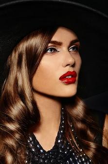Giovane donna con trucco luminoso e cappello nero