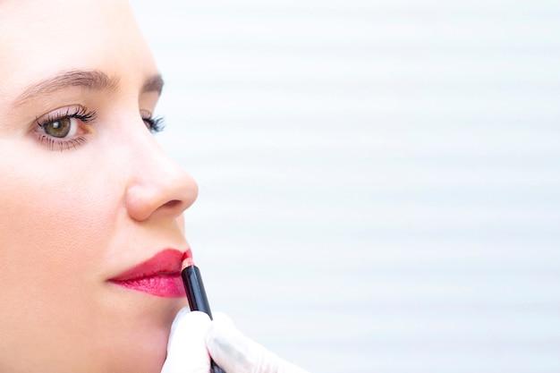 Giovane donna con trucco permanente sulle labbra al salone di estetiste. trucco permanente (tatuaggio). disegnare un contorno con una matita per labbra bianca