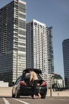 Giovane donna con un'auto nel parcheggio