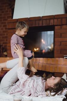 Giovane donna con un bambino. mamma e figlio stanno scherzando, divertendosi vicino al camino.