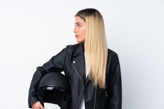 Giovane donna con un casco del motociclo sopra la parete bianca isolata che sembra laterale