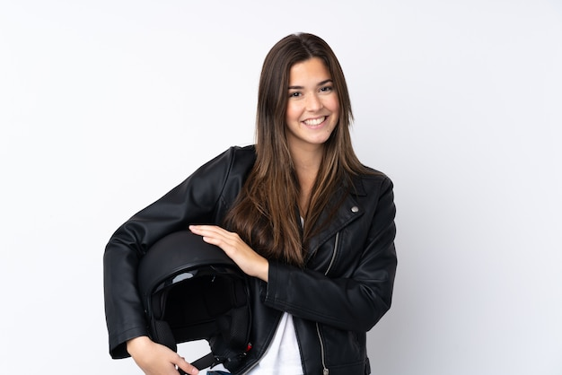 Giovane donna con un casco del motociclo sopra la risata bianca isolata della parete