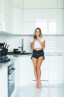 Giovane donna con un cellulare in cucina