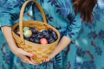 Giovane donna con un cesto di frutta, prugne e mele.
