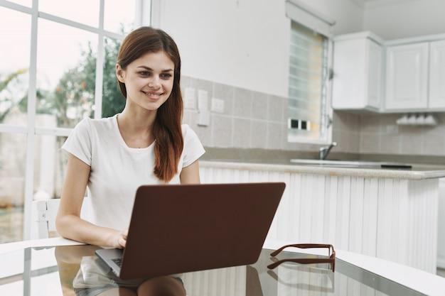 Giovane donna con un computer portatile al tavolo di lavoro e di riposo