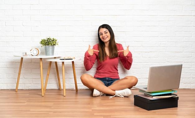 Giovane donna con un computer portatile che si siede sul pavimento al chiuso orgoglioso e soddisfatto di sé