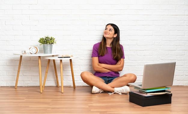 Giovane donna con un computer portatile che si siede sul pavimento all'interno che cerca mentre sorridendo