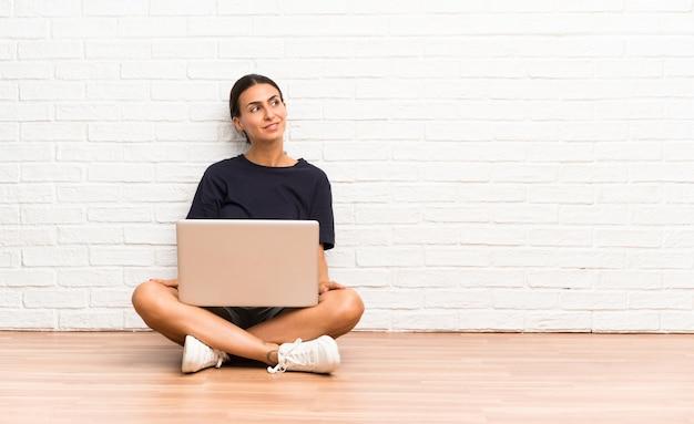 Giovane donna con un computer portatile che si siede sul pavimento che ride e che osserva in su