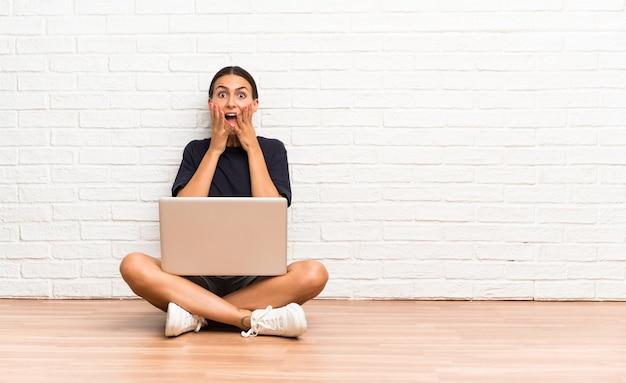 Giovane donna con un computer portatile che si siede sul pavimento con l'espressione facciale di sorpresa