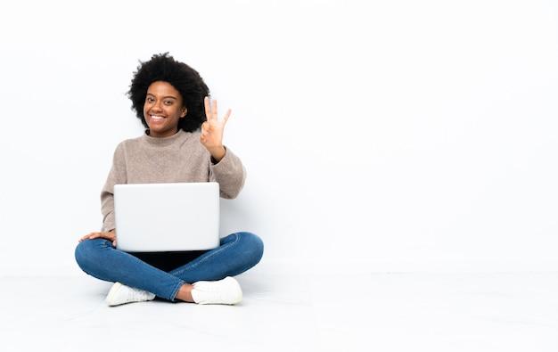 Giovane donna con un computer portatile che si siede sul pavimento felice e contando tre con le dita