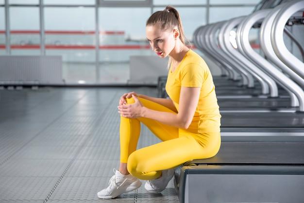 Giovane donna con un ginocchio infortunato seduto sul tapis roulant in palestra sentendo dolore dopo l'esecuzione