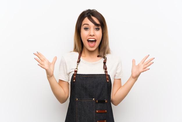 Giovane donna con un grembiule con espressione facciale scioccata
