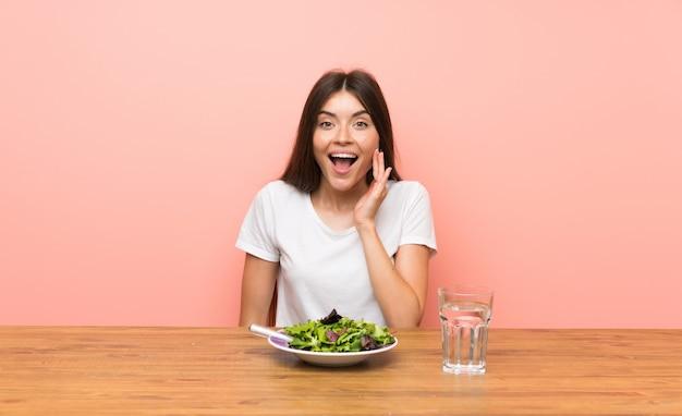 Giovane donna con un'insalata con espressione facciale sorpresa e scioccata