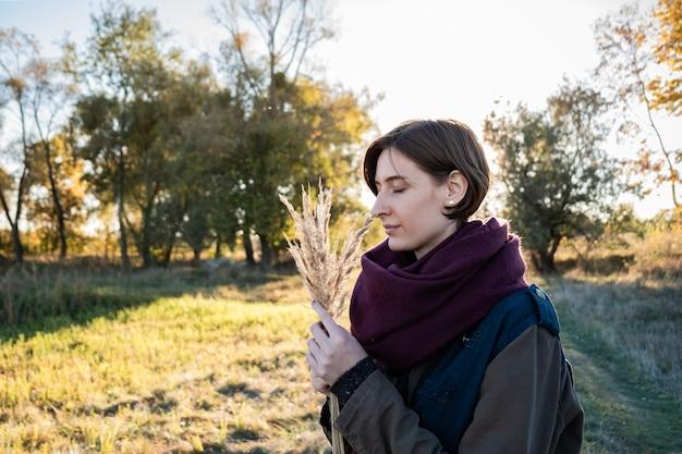 Giovane donna con un mucchio di erbe di campo godendo di una bella giornata di fine estate. ritratto di donna con gli occhi chiusi in autunno sfondo retroilluminato