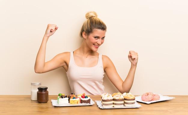 Giovane donna con un sacco di diverse mini torte in un tavolo per celebrare una vittoria