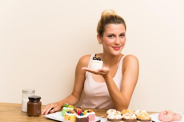 Giovane donna con un sacco di diverse mini torte in un tavolo