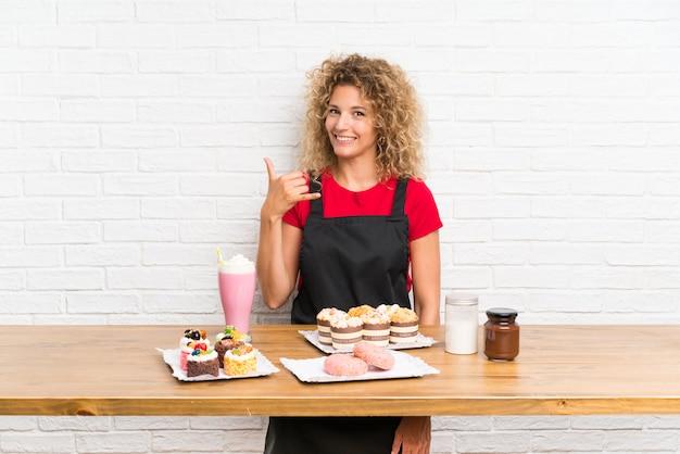 Giovane donna con un sacco di diverse mini torte in una tabella che fa il gesto del telefono