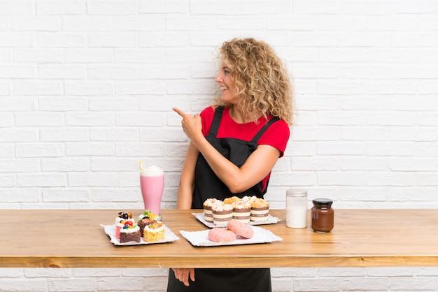 Giovane donna con un sacco di diverse mini torte in una tabella che punta indietro con il dito indice