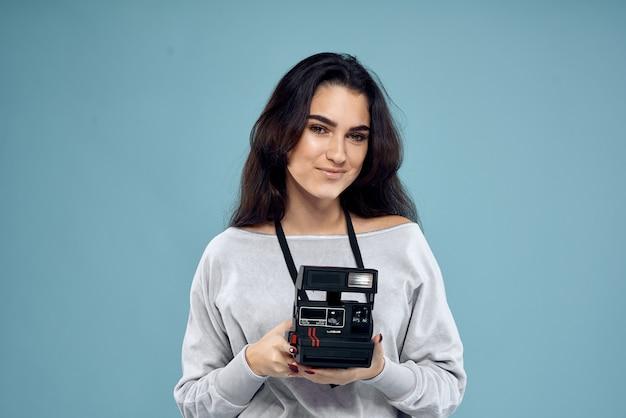 Giovane donna con un tablet, laptop e cuffie in posa su uno sfondo in studio, emozioni diverse