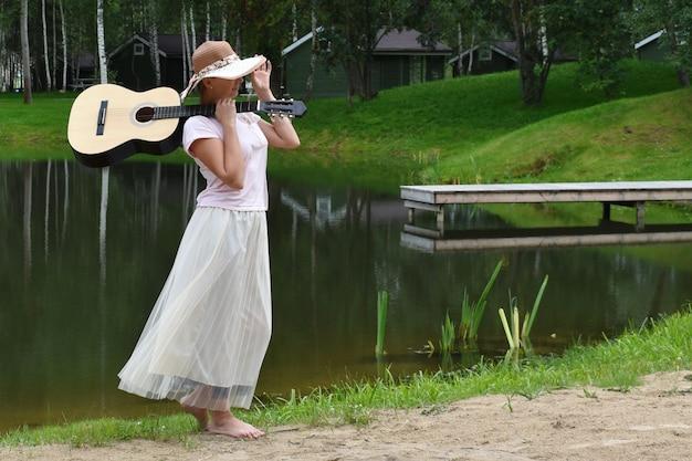 Giovane donna con una chitarra sulla natura