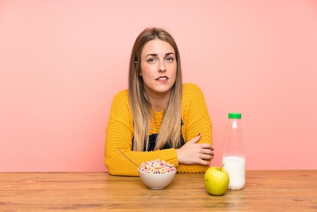Giovane donna con una ciotola di cereali con dubbi e con confondere espressione del viso
