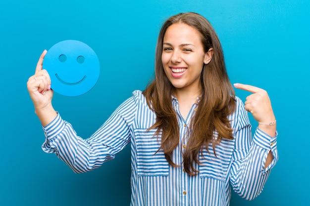 Giovane donna con una faccina sorridente su sfondo blu