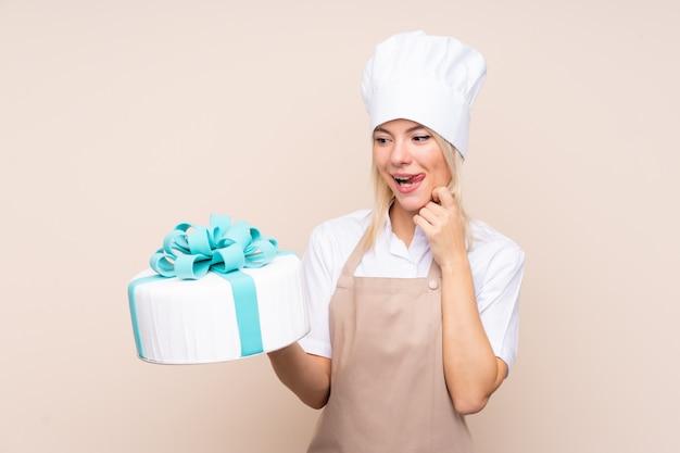Giovane donna con una grande torta sopra la parete isolata