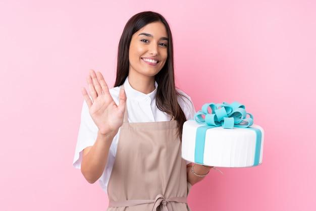 Giovane donna con una grande torta sul muro isolato salutando con la mano con espressione felice