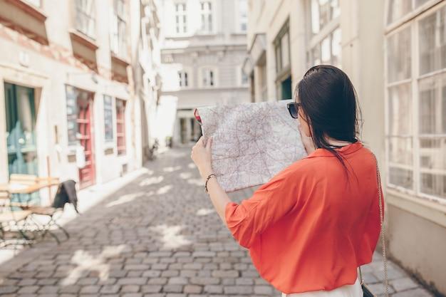 Giovane donna con una mappa della città in città. viaggia la ragazza turistica con la mappa a vienna all'aperto durante le feste in europa.