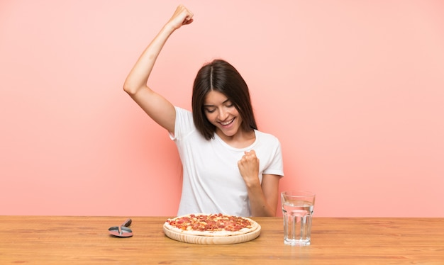 Giovane donna con una pizza che celebra una vittoria
