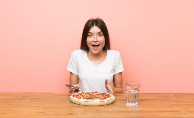 Giovane donna con una pizza in una tabella