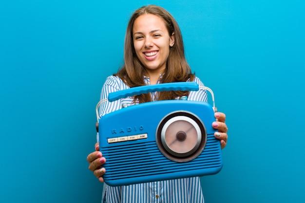 Giovane donna con una radio d'annata contro il blu