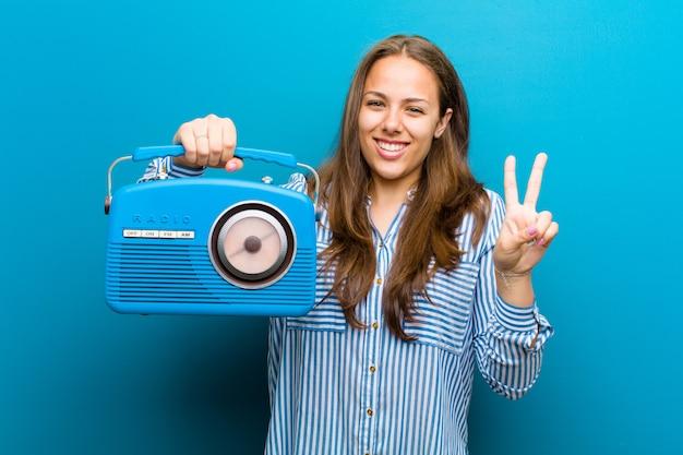 Giovane donna con una radio vintage su sfondo blu