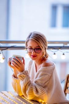 Giovane donna con una tazza di caffè vicino a luci fiabesche