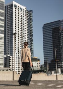 Giovane donna con una valigia in città