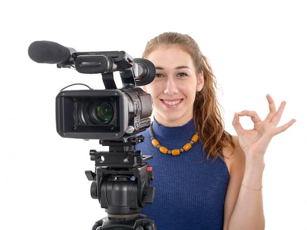 Giovane donna con una videocamera, pronta per le riprese su sfondo bianco